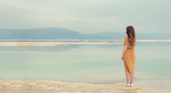 Back view of stylish girl wearing dress on seaside, Dead Sea beach. Travel, summer vacation, holiday - Stock Photo - Images