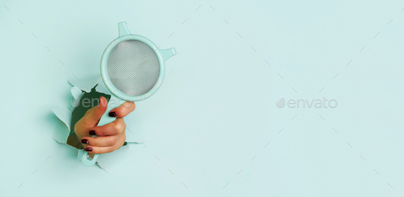 Female hand holding sieve flour through hole on blue background. Backing and cooking concept. Banner - Stock Photo - Images