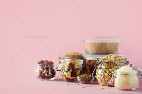 Grains, cereals, nut, dry fruits in glass jars over pink background with copy space. Clean eating - Stock Photo - Images