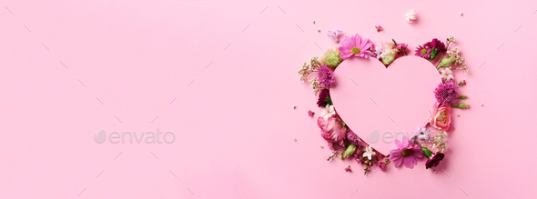 Creative layout with pink flowers, paper heart over punchy pastel background. Top view, flat lay - Stock Photo - Images