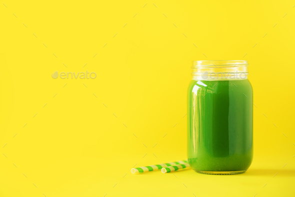 Bottle of green celery smoothie on yellow background. Banner with copy space. Fresh juice for detox - Stock Photo - Images