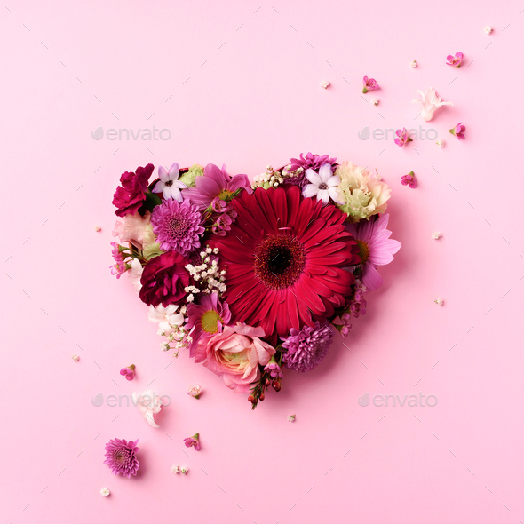 Heart shape made of spring flowers on pink punchy pastel background. Top view, flat lay. Summer - Stock Photo - Images