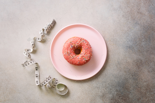 Pink donut on plate, measuring tape over grey concrete background. Diet concept. Weight lost after - Stock Photo - Images