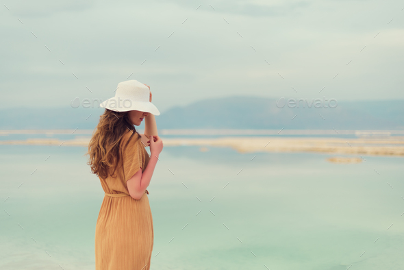 Young girl with shining blonde hair goes to seaside, Dead Sea beach. Banner. Travel, summer vacation - Stock Photo - Images