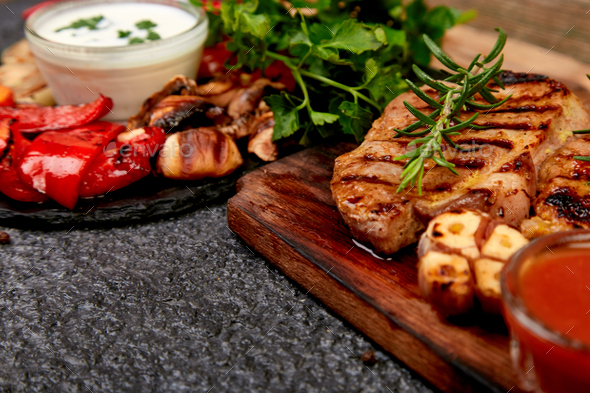 Steak pork grill on wooden cutting board with a variety of grilled vegetables. - Stock Photo - Images