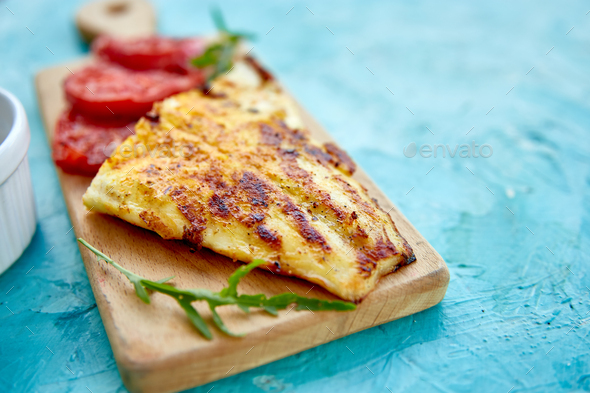 Grilled pike fillet with tomatoes on wooden board - Stock Photo - Images