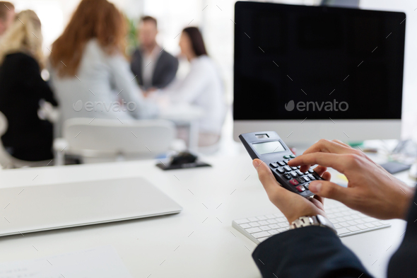 Picture of busy man using calculator in office - Stock Photo - Images
