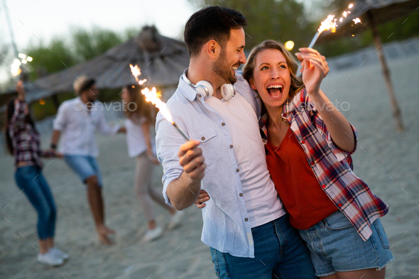 Happy group of friends lighting sparklers and enjoying freedom - Stock Photo - Images