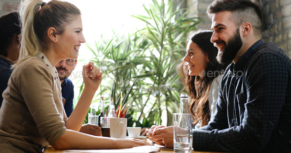 Happy colleagues from work socializing in restaurant - Stock Photo - Images