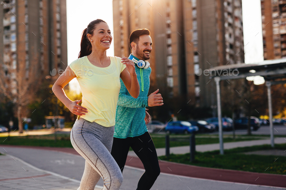Young attractive couple running outside on sunny day - Stock Photo - Images