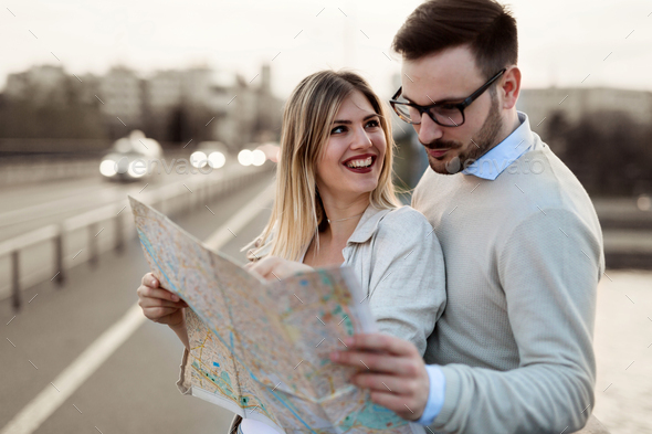 Smiling couple in love traveling with a map outdoors - Stock Photo - Images