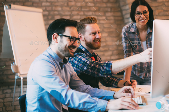 Coworkers working together as a team and discussing ideas - Stock Photo - Images