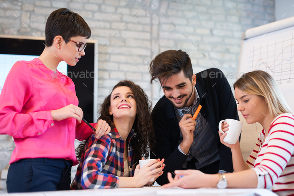 Creative young business people and architects working in office - Stock Photo - Images