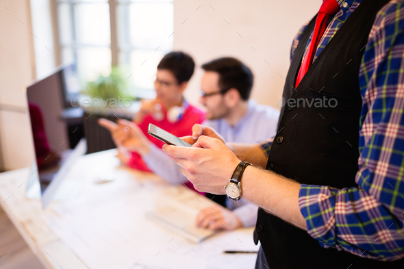 Businessman using smartphone in modern office, closeup - Stock Photo - Images