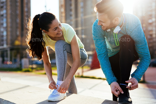 Runners tying running shoes and getting ready to run - Stock Photo - Images