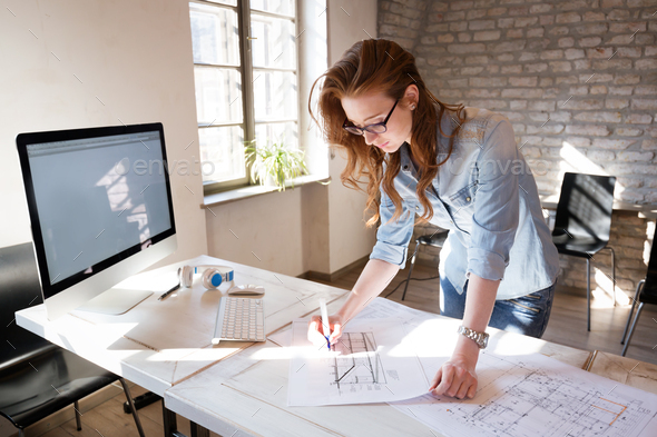 Female designer in office working on architects project - Stock Photo - Images