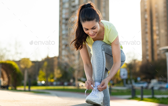 Portrait of woman taking break from jogging - Stock Photo - Images