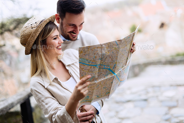 Happy tourist couple with map traveling outdoors - Stock Photo - Images