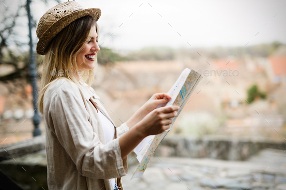 Tourist woman looking at map and exploring city - Stock Photo - Images