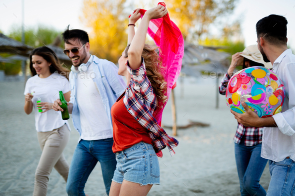 Group of happy young people playing with ball on beach - Stock Photo - Images