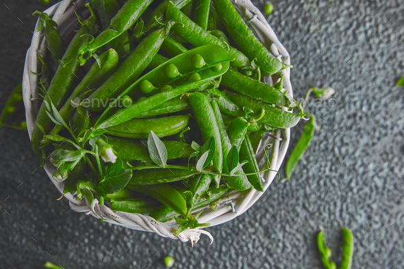 White Basket with fresh green peas on black background. - Stock Photo - Images