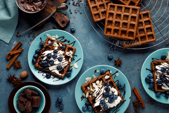 Chocolate belgian waffles with ice cream and fresh blueberry on blue background, top view - Stock Photo - Images