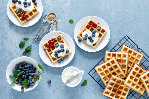Traditional belgian waffles with cream cheese and fresh blueberry on blue background, top view - Stock Photo - Images