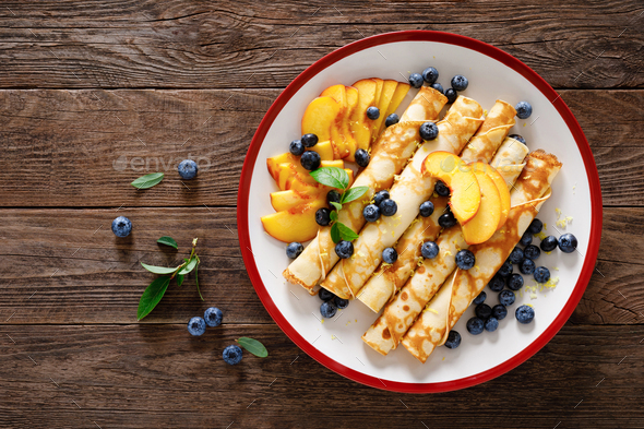 Sweet crepes filled with fresh blueberry and peach - Stock Photo - Images