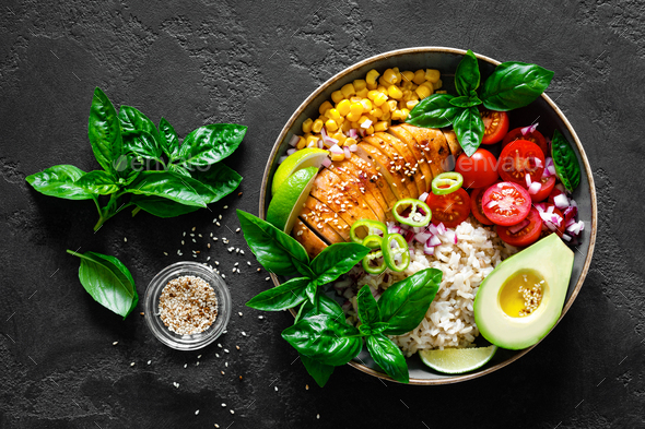 Grilled chicken breast lunch bowl with fresh tomato, avocado, corn, red onion, rice and basil - Stock Photo - Images