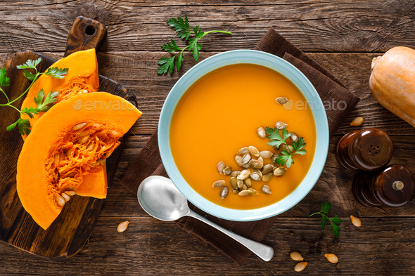 Pumpkin soup. Vegetarian soup with pumpkin seeds in bowl on wooden table, top view - Stock Photo - Images