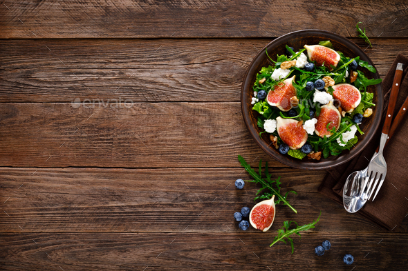 Fig salad with goat cheese, blueberry, walnuts and arugula on wooden background - Stock Photo - Images