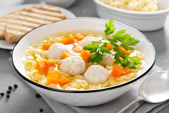Hot chicken soup, broth with meatballs, carrot, pasta and fresh parsley - Stock Photo - Images