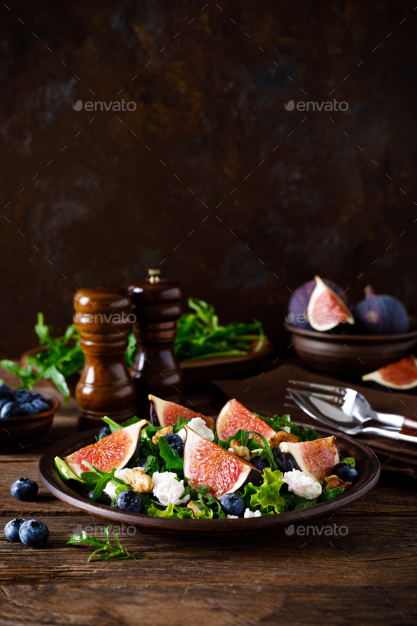 Fig salad with goat cheese, blueberry, walnuts and arugula on wooden background. Healthy food. Lunch - Stock Photo - Images