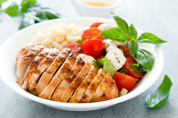 Grilled chicken lunch bowl with orange juice dressing, pasta and caprese salad - Stock Photo - Images