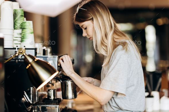 A youthful pretty thin blonde with long hair,dressed in casual outfit,is cooking coffee in a modern - Stock Photo - Images