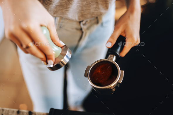 A young pretty slim girl,wearing casual outfit,is cooking coffee in a modern coffee shop. It focuses - Stock Photo - Images
