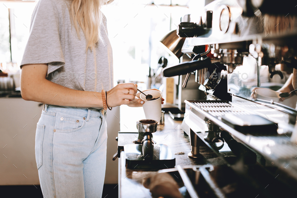 A youthful thin blonde lady,wearing casual clothes,stands nexrt to the coffee machine in a cozy - Stock Photo - Images