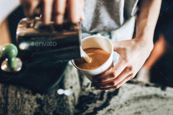 A young good looking blonde,wearing casual style,holds a glass and milk frother in a cozy coffee - Stock Photo - Images