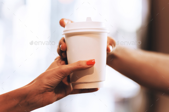 Barista passes coffee to a visitor in a popular coffee shop, hands and a glass of coffee are shot - Stock Photo - Images