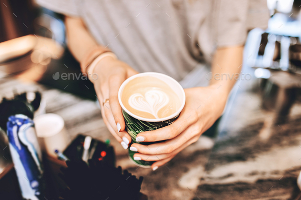 A youthful slim lady,dressed in casual clothes,is holding a coffee next to coffee machine in a - Stock Photo - Images