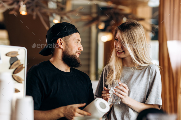 Two young smiling people,a blonde girl and man with beard.dressed in casual outfit, stand next to - Stock Photo - Images
