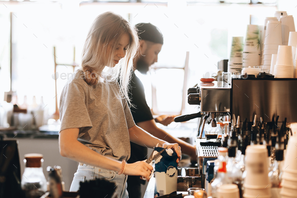 A young beautiful thin blonde, dressed in casual clothes, opens the milk next to the coffee machine - Stock Photo - Images