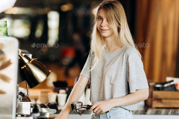 A cute blonde youg girl,wearing casual outfit,stands next to the coffee machine and smile in a cozy - Stock Photo - Images