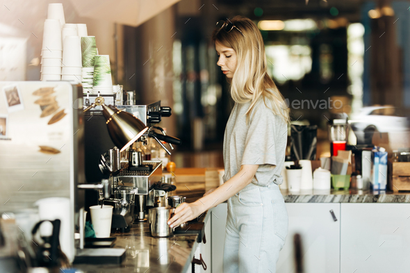 A young pretty thin blonde with long hair,dressed in casual outfit,is cooking coffee in a modern - Stock Photo - Images