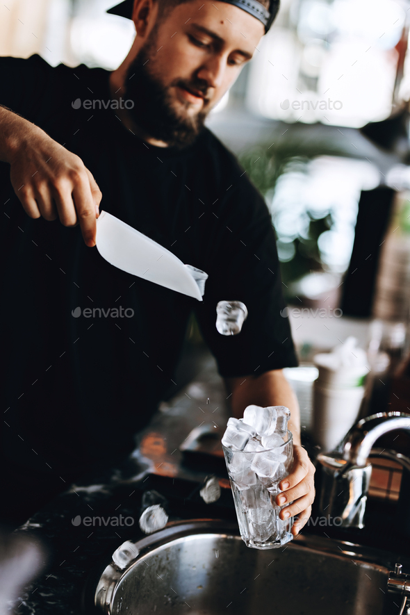 A young handsome man with beard,wearing casual clothes,puts some ice into the glass in a cozy coffee - Stock Photo - Images