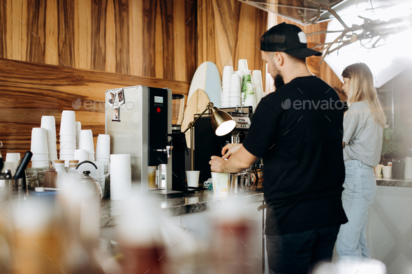 A young stylish man with beard,dressed i casual style,is cooking coffee in the expensive coffee - Stock Photo - Images
