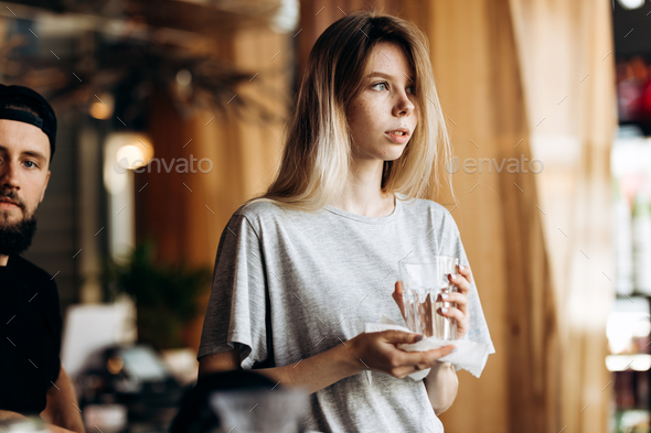 A youthful pretty blonde girl,dressed in casual style, holds a clean glass and looks at the window - Stock Photo - Images