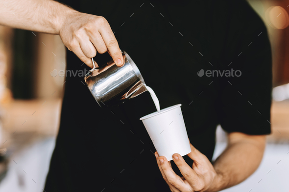 Barista carefully pours the milk into a glass in a modern coffee shop - Stock Photo - Images
