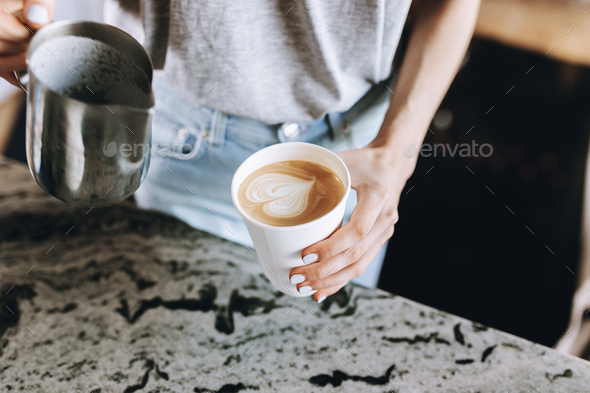 A youthful slim kind blonde girl,dressed in casual outfit,skillfully adds milk to coffee in a modern - Stock Photo - Images