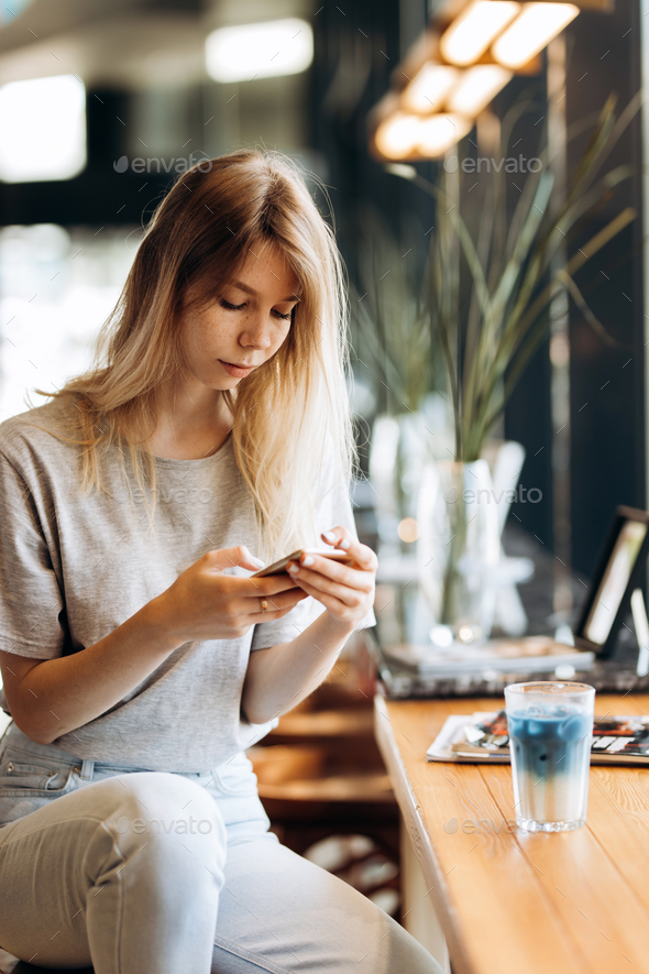 A cute thin blonde girl,dressed in casual style,drinks coffee and looks at her phone in a coffee - Stock Photo - Images